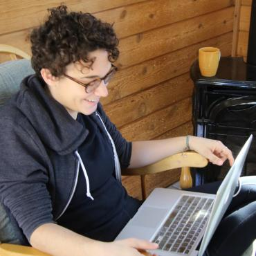 The writer, smiling, sits cross-legged in a chair, laptop on her lap.