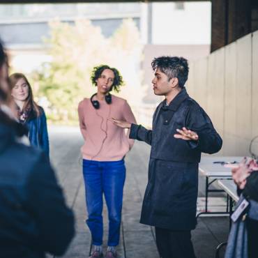 The artist in a black trenchcoat and pants outdoors speaking to an audience of playtesters