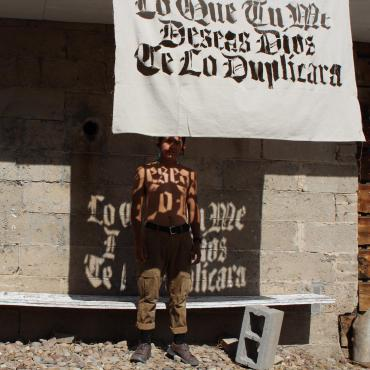 "Sun shines through a canvas stencil rendering black letter text on a shirtless brown body—the text reads ""Todo Lo Que Me Deseas Dios Te Lo Duplicara""."
