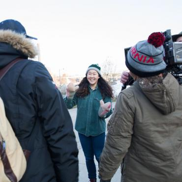 "Naomi Ko is in the center of the photo surrounded by various crew members during the production of ""Nice."""