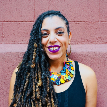 Locks pulled over to one side, multi-colored necklace made of West-African cloth buttons, black tank top, fuschia lipstick, and smiling golden brown face.