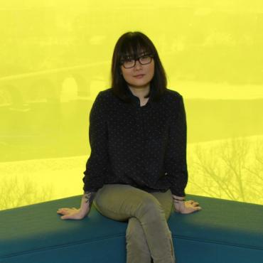 Su Hwang seated, top floor at the Guthrie Theater, bright yellow background overlooking the Stone Arch Bridge.