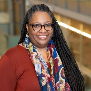 Sherrie Fernandez-Williams, a fifty-year-old black woman writer with dreadlocks smiling at the camera