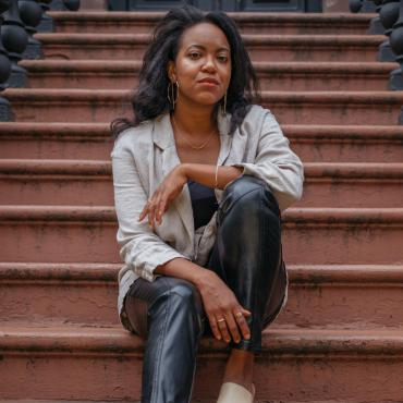 Whitney White, an African American woman, seated in front of a brown stone in Crown Heights, Brooklyn.