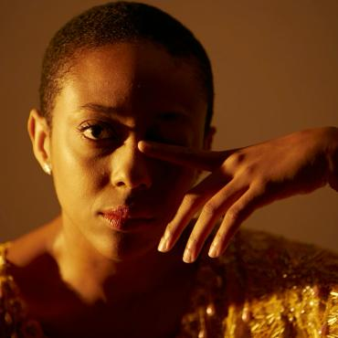 A brown skin Black woman with a buzz cut stares at the camera with her right eye wide open and left eye closed by her left index finger. She is wearing a shimmering orange top, gold lightning bolt earrings, and pink lipstick.