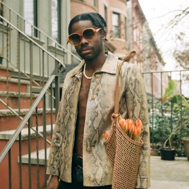 Prince Harvey standing on a Brooklyn stoop dressed in snakeskin jacket, a string of pearls and leather pants, with a bouquet of tulips in a tote bag tucked under his arm, December 2020.