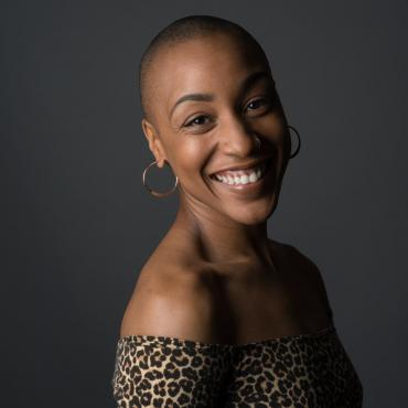 Vie Boheme, a thirty-something Black woman, multimodal performance artist with a bald fade hair cut smiling for a headshot over her right shoulder.