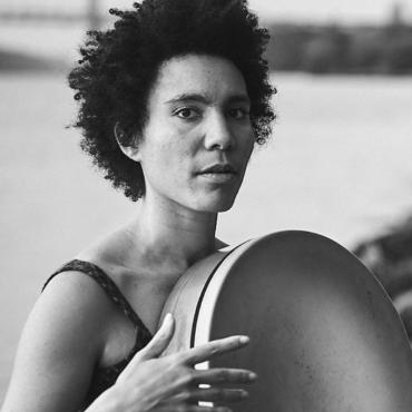 Anaïs Maviel, a thirty-year-old androgynous woman of color, posing with a frame drum in front of the Hudson River in New York City.