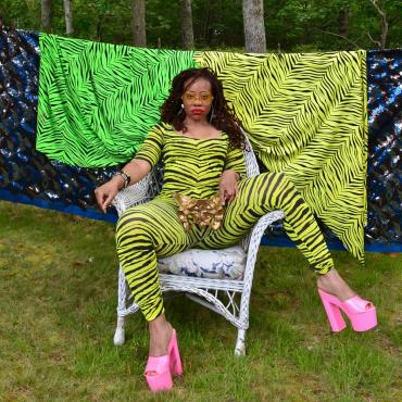 Black woman in neon green zebra print body suit sitting with legs open and hot pink stacked heels on and a golden pelvis bone placed at her crotch.