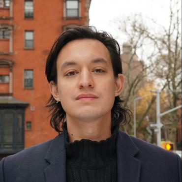 Headshot of Kyle Dacuyan in front of a red brick building and traffic lights