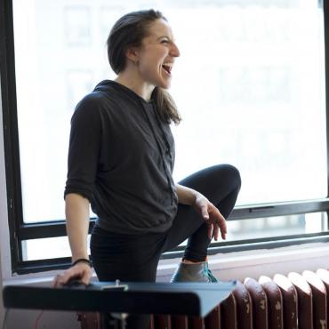 Ephrat Asherie, a thirty-something white woman laughing during a rehearsal with one foot up on a radiator.