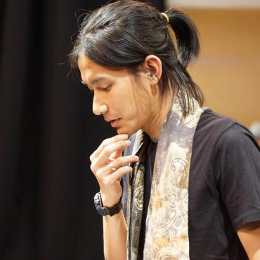 Jay Afrisando, a thirty-something Asian man composer/sound artist, with his right index and thumb on his chin as he pauses his speech during a concert opening.
