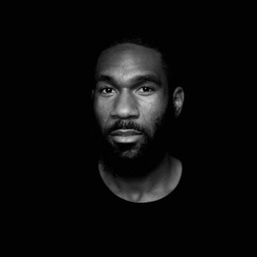 In a black and white portrait, Justin pools in a pitch black background. He's a twenty-something Black man with a full beard and a calm and intent gaze.