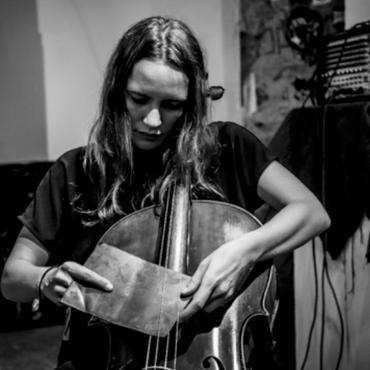 Leila Bordreuil, a thirty something white woman, playing the cello with a large piece of scrap metal placed under the strings on her fingerboard.