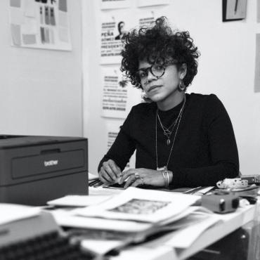 Lizania, a thirty-seven-year-old lighter skin Black woman with black short curly hair. With large glasses, large earrings sitting at her desk with her arms propped on it. You can see her typewriter as well as a black printer.