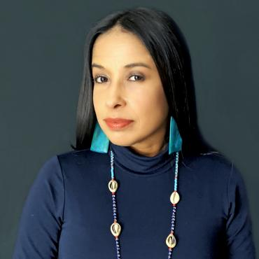 Headshot of the Latinx poet Peggy Robles-Alvarado wearing a sacred beaded necklace of cowrie shells with dark and light blue beads and large light blue rectangular earrings.