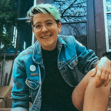A thirty-year old white non-binary person with short hair kneeling in boots and a jean jacket.
