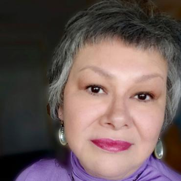A 56 year old woman looking directly into the camera wearing a lavender turtleneck and wampum necklace.