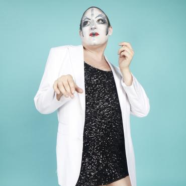 performer in short, black sequined dress and white dinner jacket wearing gender nonconforming makeup