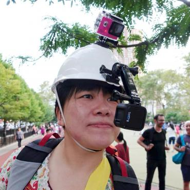 Ying Liu, an Asian woman wearing a white hard hat mounted with two GoPro Cameras, looks on.