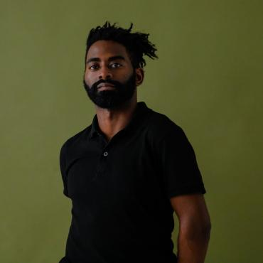 Jerron, a Black man with full beard and short locks wearing black, stands stoically in front of a green background.