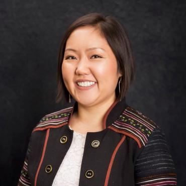 Joua Lee Grande, a Hmong-American woman wearing a blazer with Hmong designs sewn on the shoulders and arms smiling at the camera.